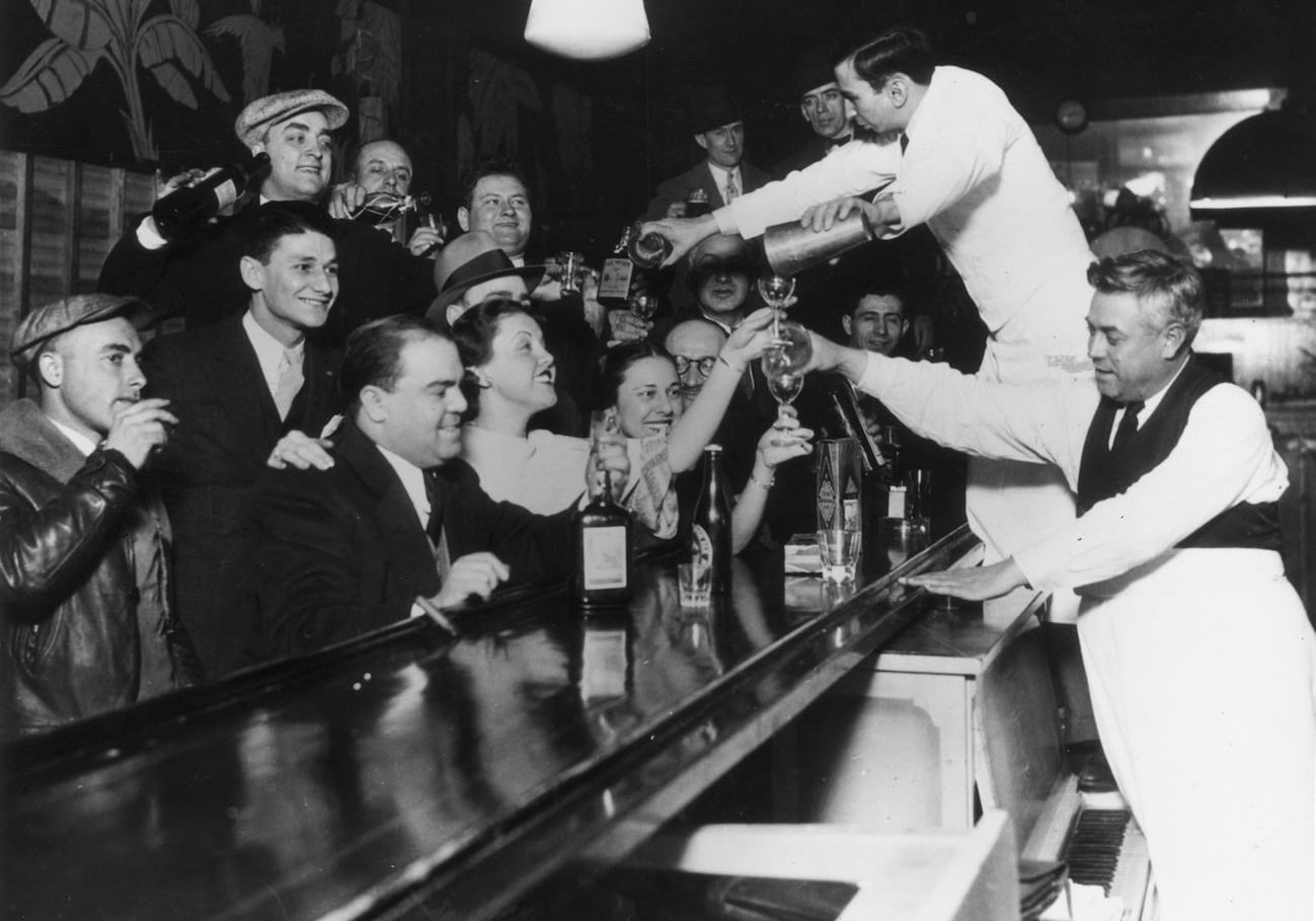 Bartenders at Sloppy Joe's bar pour a round of drinks on the house for a large group of smiling customers as it was announced that the 18th Amendment had been repealed and Prohibition had been removed from the US Constitution after 13 years, Chicago, Illinois  (Photo by American Stock/Getty Images)